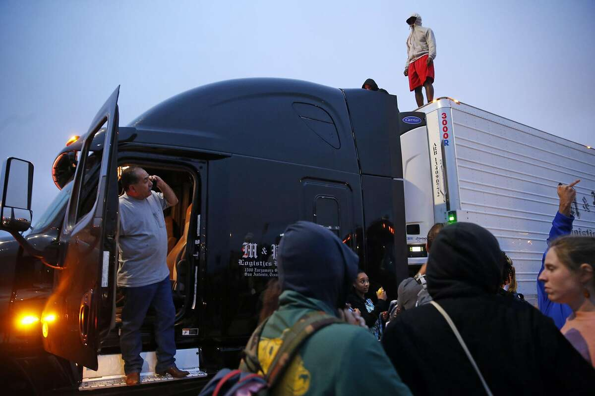 Truck driver Eddie Saenz of San Antonio calls his trucking company as protesters stand on his trailer after marchers shut down I-880 during Oakland protest against recent police shootings on Thursday, July 7, 2016.