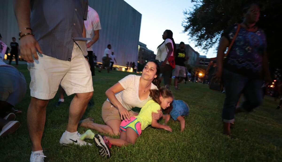 A mother covers her children as Dallas police respond to shots being fired during a protest over recent fatal shootings by police in Louisiana and Minnesota, Thursday, July 7, 2016, in Dallas. Snipers opened fire on police officers during protests; several officers were killed, police said. (Maria R. Olivas/The Dallas Morning News via AP)