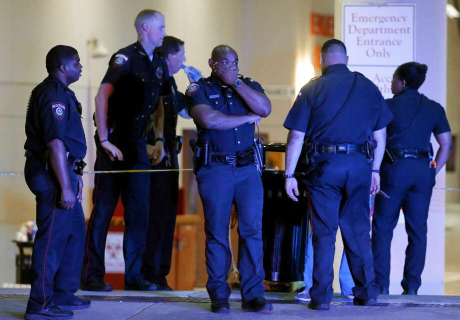 A Dallas police officer covers his face as he stands with others outside the emergency room at Baylor University Medical Center, Friday, July 8, 2016, in Dallas. Snipers opened fire on police officers in the heart of Dallas on Thursday night, killing some of the officers. Photo: Tony Gutierrez/AP