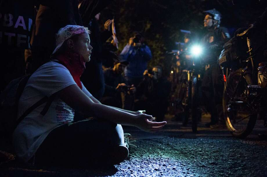 A Black Lives Matter protester sits in front of a Seattle police line blocking an Interstate 5 onramp with tears in her eyes and hands open, Thursday, July 7, 2016. The protest followed the fatal police-involved shootings of Alton Sterling in Louisiana and Philando Castile in Minnesota earlier this week. Photo: GRANT HINDSLEY, SEATTLEPI.COM / SEATTLEPI.COM