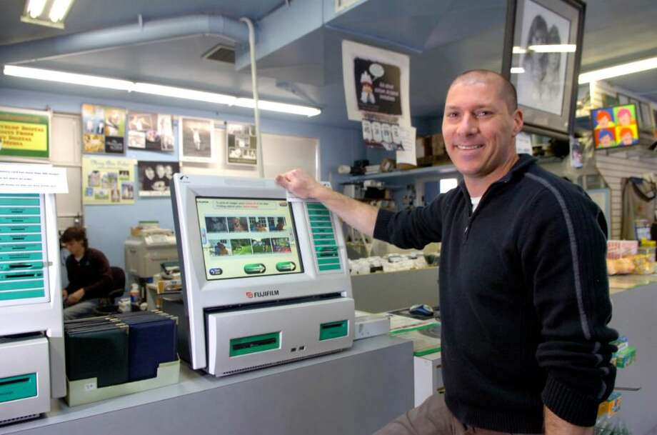 Craig Ketover, at PD Photo on Boulder Avenue in Old Greenwich, standing next to new photo kiosks. Ketover's photography business has experienced rapid change in the last 10 years and has survived. Photo: Helen Neafsey, ST / Greenwich Time