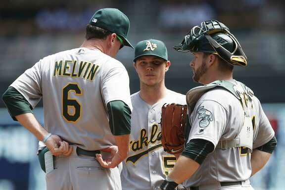 Oakland Athletics manager Bob Melvin, left, pays a visit to the mound with pitcher Sonny Gray and catcher Stephen Vogt, right, in the fifth inning of a baseball game against the Minnesota Twins, Wednesday, July 6, 2016, in Minneapolis. The Twins won 4-0. (AP Photo/Jim Mone)