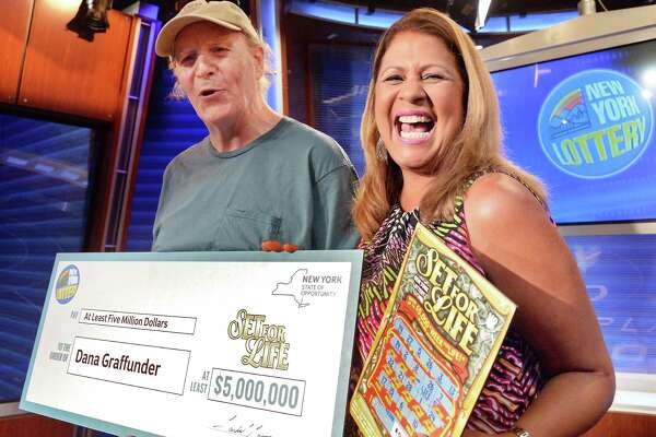 Recently retired warehouse worker Dana Graffunder, left, of Voorheesville receives an over-sized prize check worth $5,000,000 from NY LotteryOs Yolanda Vega during a news conference Friday July 8, 2016 in Schenectady, NY.  (John Carl D'Annibale / Times Union)