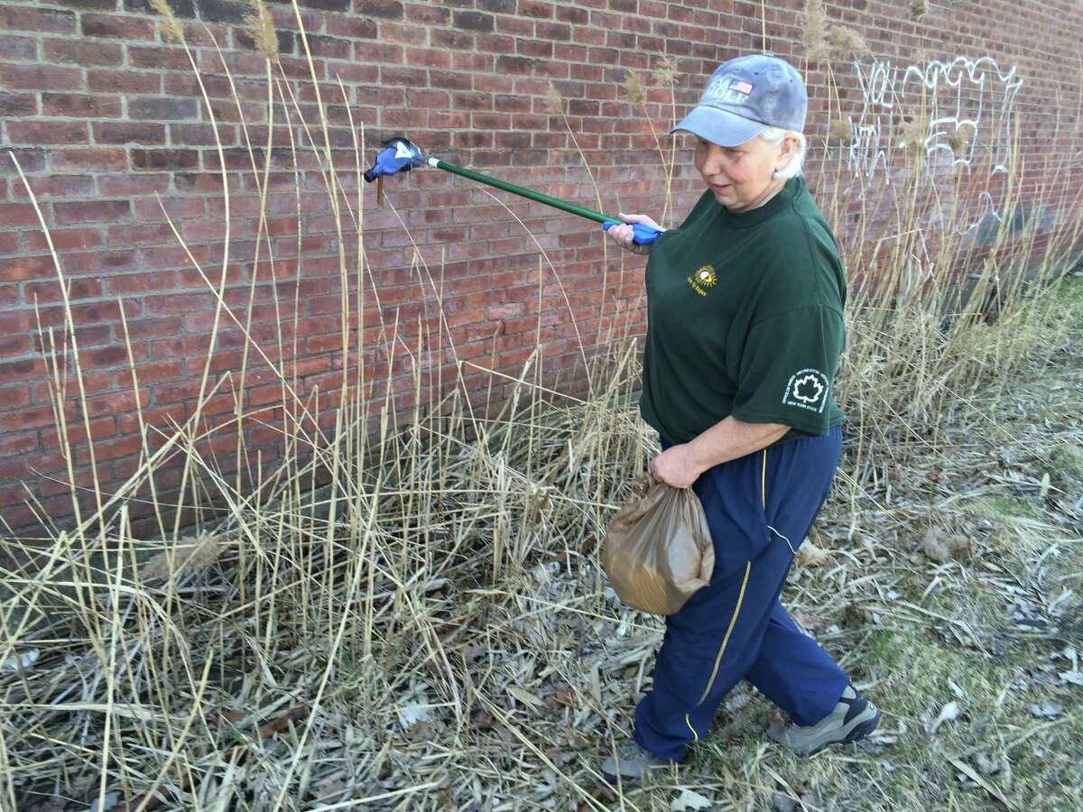 Grenada Terrace resident Sue Trevellyan is seen picking up garbage outside the former Al Tech Specialty Steel site April 17, 2016 on Spring Street Road in Colonie. Trevellyan, who regularly takes walks on the road, said ever since the plant closed there has been more dumping and vandalism around the abandoned property.
