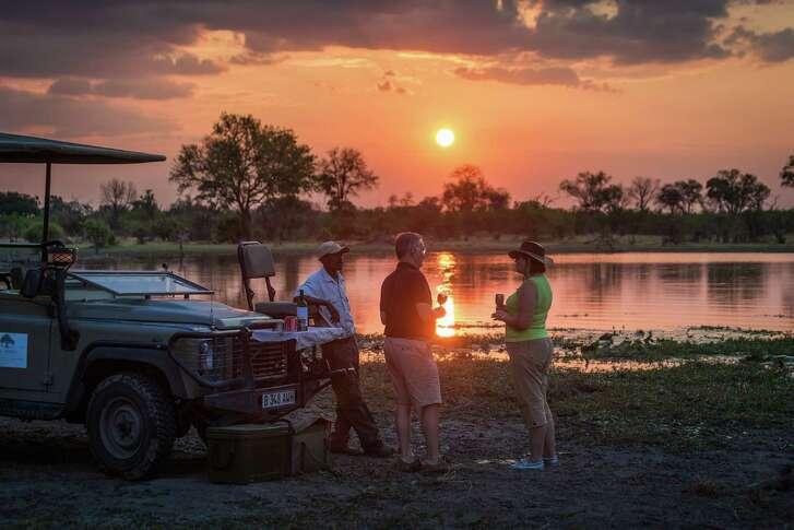 Guests at Machaba Camp in Botswana's Okavango Delta enjoy a post-safari glass of wine while soaking in the sunset.