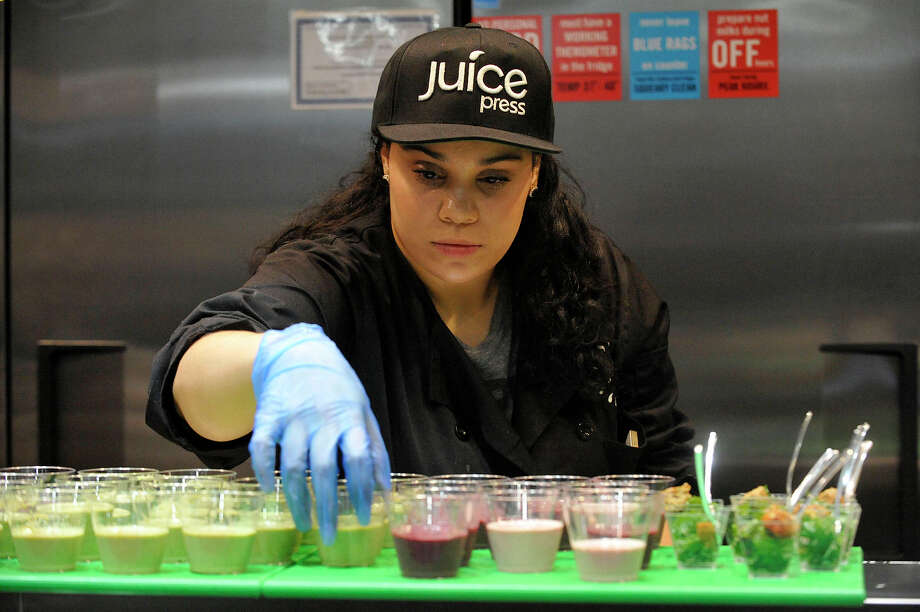 Jaden Pabon organizes free samples during an opening party for the first Juice Press on Greenwich Avenue in Greenwich in 2015. Photo: Jason Rearick / Jason Rearick / Stamford Advocate