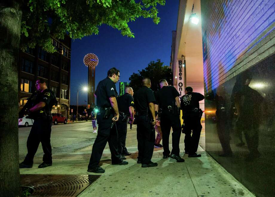 Dallas police officers clear the area of the Greyhound bus station after shots were fired during a protest on Thursday in Dallas.  (Ashley Landis/The Dallas Morning News via AP) Photo: Ashley Landis, MBR / The Dallas Morning News