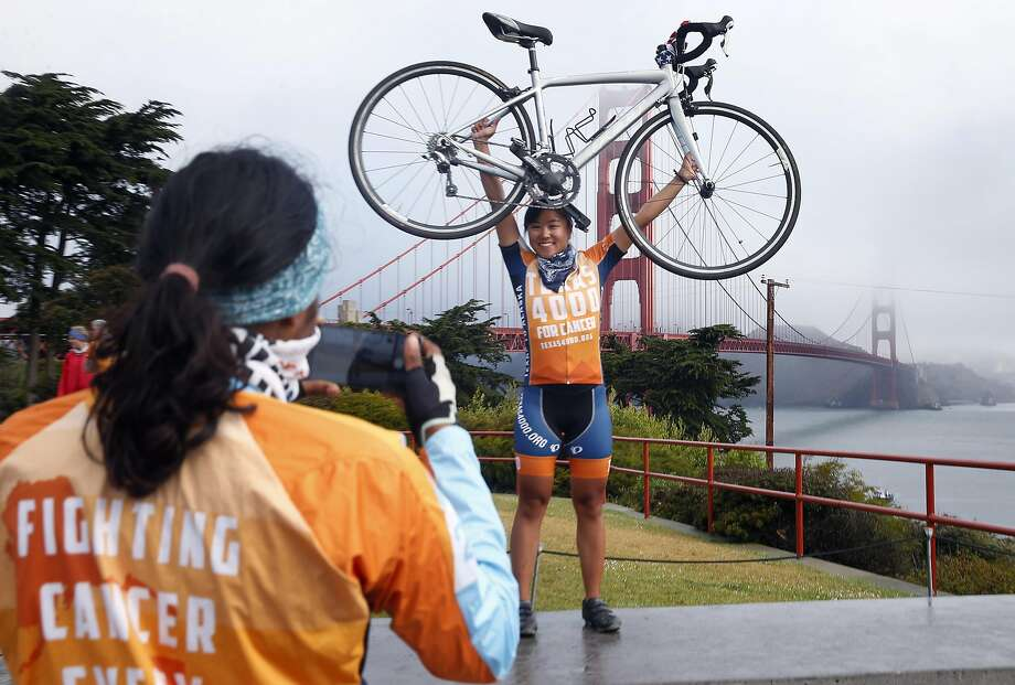 Helen Tang has her photo snapped by Madhushree Zope before they bicycle across the Golden Gate Bridge. Photo: Paul Chinn, The Chronicle