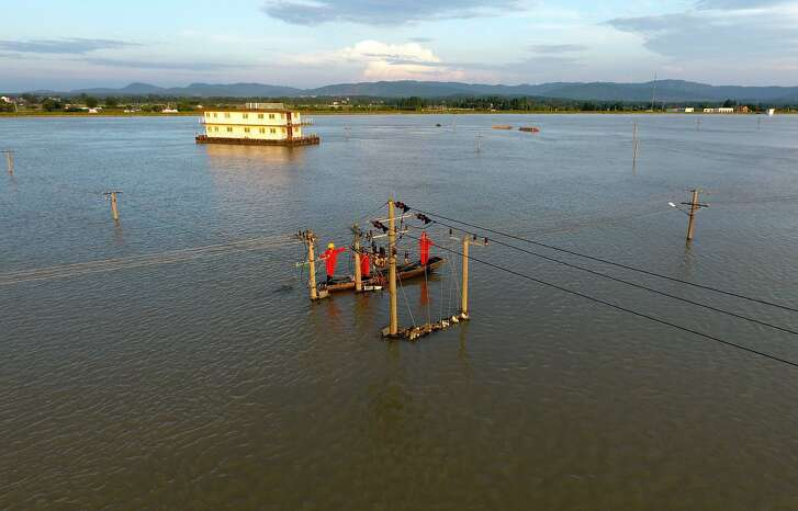 TOPSHOT - This photo taken on July 7, 2016 shows workers restoring electricity to a flooded village near the town of Shuiyang in Xuancheng, in east China's Anhui province. Flooding is common during the summer monsoon season in southern China, but rainfall has been particularly heavy this year and many areas have been lashed by torrential rains this week. / AFP PHOTO / STR / China OUTSTR/AFP/Getty Images