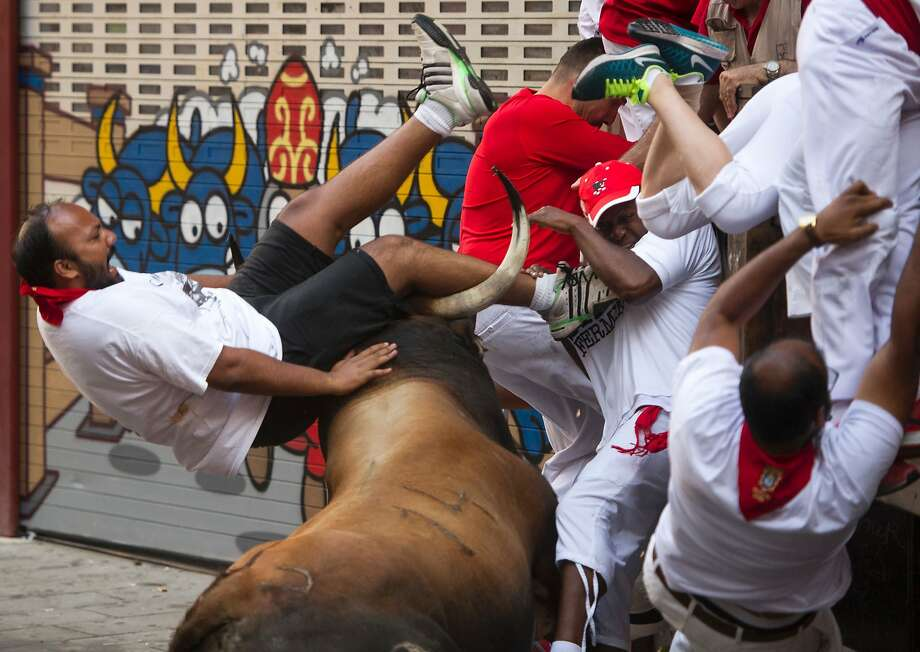 A fighting bull gores a participant during the second day of the bull run in Pam plona, Spain. Two men were in serious condition after being gored. Photo: MIGUEL RIOPA, AFP/Getty Images