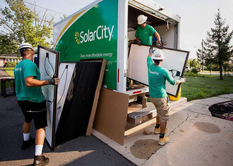 SolarCity Corp. employees unload solar panels from a truck during a home installation in Kendall Park, New Jersey, in 2015.  Photo: Michael Nagle, Bloomberg