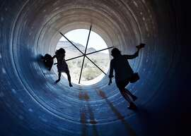 NORTH LAS VEGAS, NV - MAY 11:  People walk through a Hyperloop tube after the first test of a propulsion system at the Hyperloop One Test and Safety site on May 11, 2016 in North Las Vegas, Nevada. The company plans to create a fully operational hyperloop system by 2020.  (Photo by David Becker/Getty Images,)