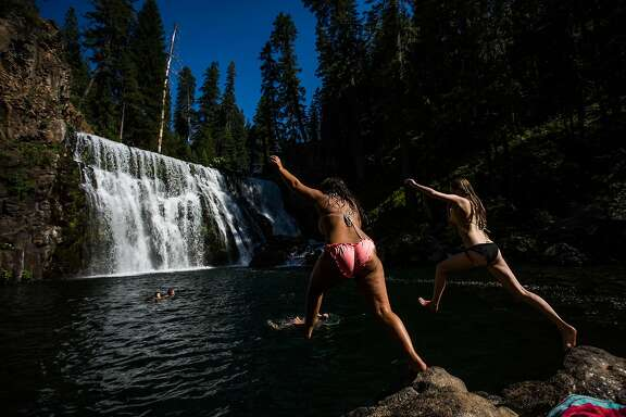 Sierra Klaus, 14, left, and Alana Fraley, 15, right, jump into a pool below Middle Falls on the McCloud River near McCloud, California, June 29, 2016.