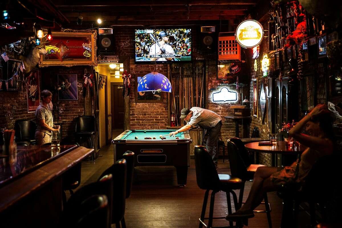 Ward Wilson, center, plays pool at The Diggin's bar in Weaverville, California, June 30, 2016.