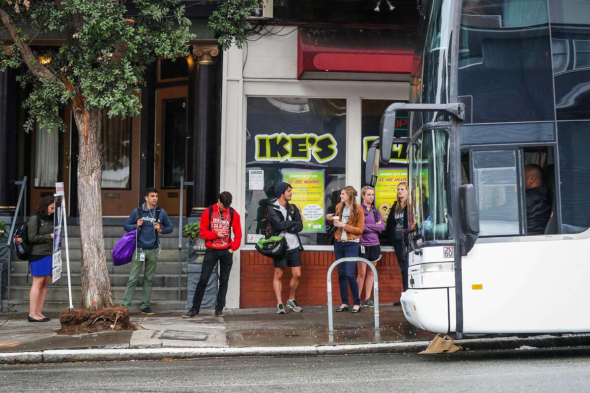 People line up to board a tech bus on 16th and Sanchez Streets in the Mission District, in San Francisco, California, on Friday, July 8, 2016.