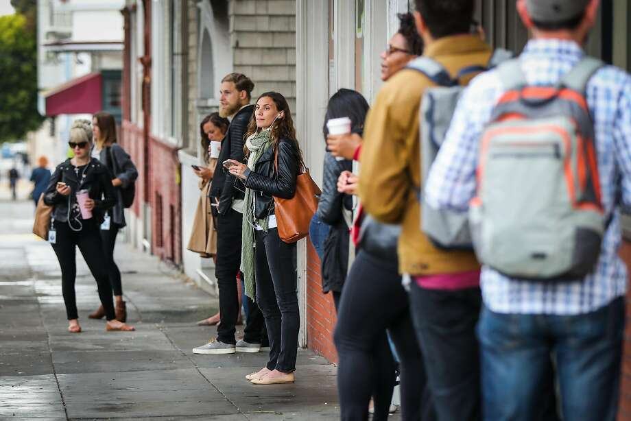 Workers stand along 16th Street as they wait for a tech bus to arrive in the Mission District. Photo: Gabrielle Lurie, Special To The Chronicle