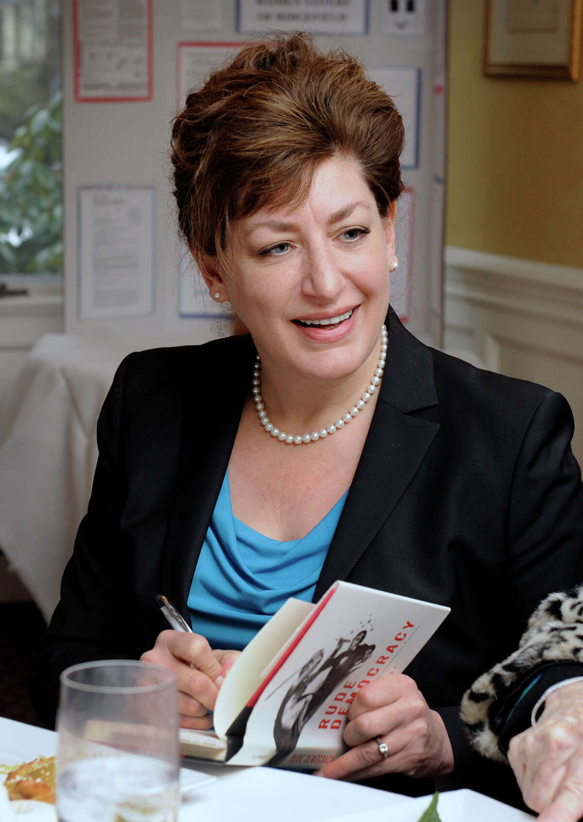 """Susan Herbst, president of the University of Connecticut, speaks to a gathering sponsored by the Ridgefield League of Women Voters, at Sarah's Wine Bar in Ridgefield, Friday, January 11, 2013. After the talk, Herbst signs copies of her book """"Rude Democracy."""""""