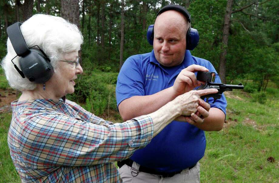 In this April 30, 2016 photograph, Jake Driskell, a Laurel police officer and owner of Gun Guy Tactical, helps Crestview Baptist Church member and first time shooter Katherine Huffman, line up her sights with her husband's revolver during the live fire portion of a enhanced concealed carry class sponsored by the church for members and area residents in Petal, Miss. The 20 participants received hands on assistance during a practical shooting exercise, a thorough review on the fundamentals of safe handling of firearms in addition to a review of the basic and enhanced Mississippi Concealed Carry laws. (AP Photo/Rogelio V. Solis) Photo: Rogelio V. Solis / Associated Press / AP