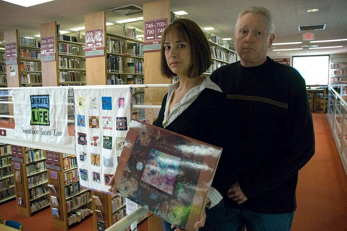 Janis and Ronald Wohlschlaeger hold a picture of the square they donated to the Loving Squares Donor Family Quilt, hanging behind them at the New Milford Public Library Tuesday.