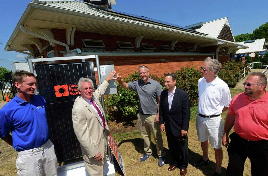 Local dignitaries and Direct Energy Solar staff including Direct Energy Solar project lead, Brett Avelin, Norwalk Mayor Harry Rilling, The Mayor's Energy and Environment Task Force Chairman John Kydes, State Senate Majority Leader Bob Duff, councilman Tom Livingston and Norwalk Recreation and Parks Director Mike Mocciae present the new solar panels on the bath houses at Calf Pasture Beach in Norwalk during a press conference on Wednesday. Photo: Erik Trautmann / Hearst Connecticut Media / Norwalk Hour