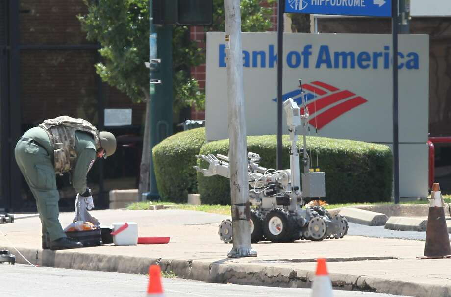 A McLennan county bomb expert checks out an unidentified ice chest and luggage, Saturday, Aug. 22, 2015, in Waco, Texas. Law enforcement officers cleared portions of downtown Waco during a biker rally in protest of the handling of the Twin Peaks restaurant shooting. The sheriffs office bomb squad deployed a robot Saturday to investigate the contents, but found no hazardous materials. (Jerry Larson/Waco Tribune-Herald via AP) Photo: Jerry Larson, Associated Press