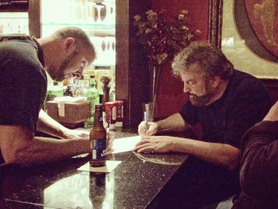 Tim Guzda, designer at Hearst Connecticut Media Group and Mackenzies bartender-at-large, drawing with artist Alan Reingold at Mackenzie's Bar & Grill in Stamford on Thursday night. Photo: Contributed / Contributed Photo / Greenwich Time Contributed