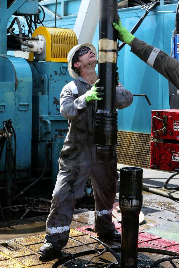 Floor hands guide drilling pipe on an oil drilling rig in the Eagle Ford Shale, where Pioneer Natural Resources has divested some of its holdings. Photo: John Davenport /San Antonio Express-News / ©San Antonio Express-News/John Davenport