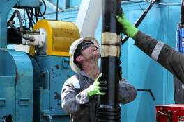 Floor hands guide drilling pipe on an oil drilling rig in the Eagle Ford Shale, where Pioneer Natural Resources has divested some of its holdings.