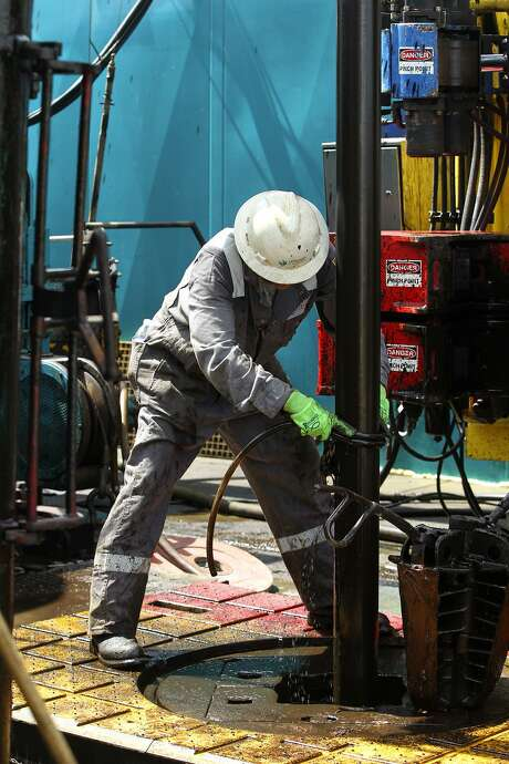 A floor hand cleans off excess oil on a well being drilled in Atascosa County near Jourdanton. In South Texas' Eagle Ford Shale, there were nine deals worth $2.4 billion in 2016, according to the PwC. Photo: John Davenport /San Antonio Express-News / ©San Antonio Express-News/John Davenport