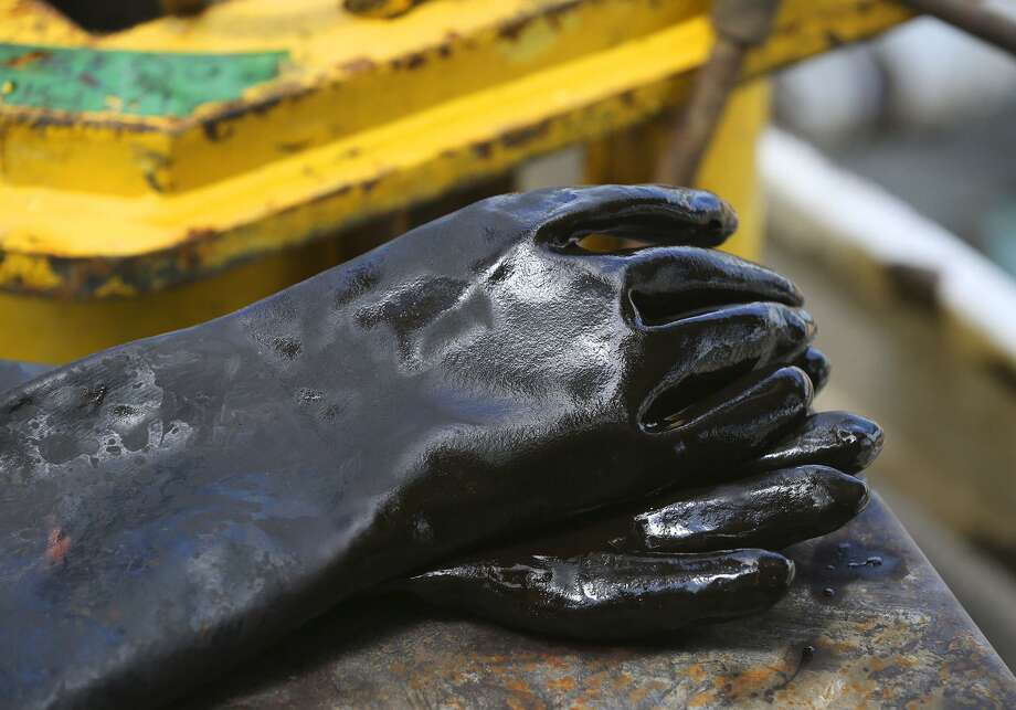 Oil covered gloves are placed on the Abraxas Petroleum Bullseye 101H well Monday June 27, 2016 in Atascosa County near Jourdanton, Texas. Even as some oil companies like Royal Dutch Shell and BP predict oil demand will peak before 2040 — as electric vehicles hit the road and governments worldwide work to cut greenhouse gas emissions — there are plenty within the oil industry who view such predictions with a healthy skepticism. Photo: John Davenport /San Antonio Express-News / ©San Antonio Express-News/John Davenport