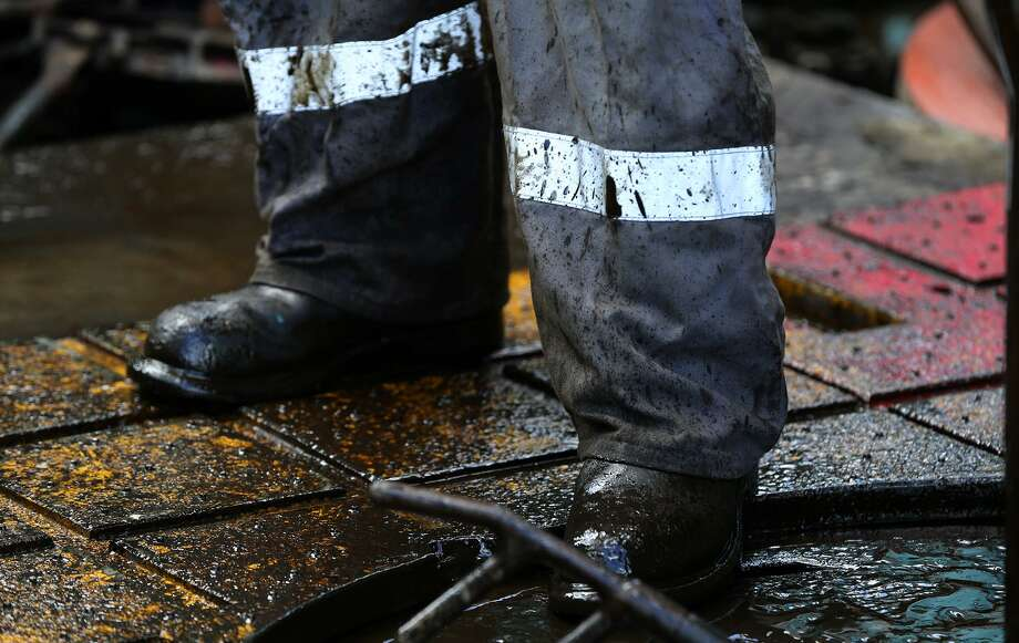 A floor hand works on Abraxas Petroleum's Bullseye 101H well Monday June 27, 2016 in Atascosa County near Jourdanton, Texas. The Eagle Ford pumps 1.2 million barrels of oil per day, and last week 70 drilling rigs were at work in the region, according to the service firm Baker Hughes. Photo: John Davenport /San Antonio Express-News / ©San Antonio Express-News/John Davenport