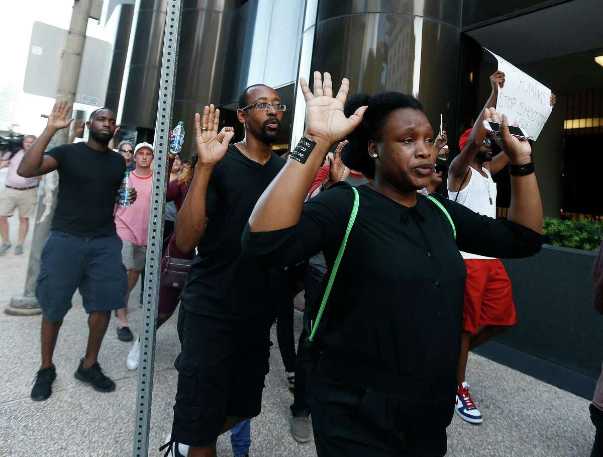 Protesters hold up their hands up as they march from Discovery Green to City Hall on Friday.