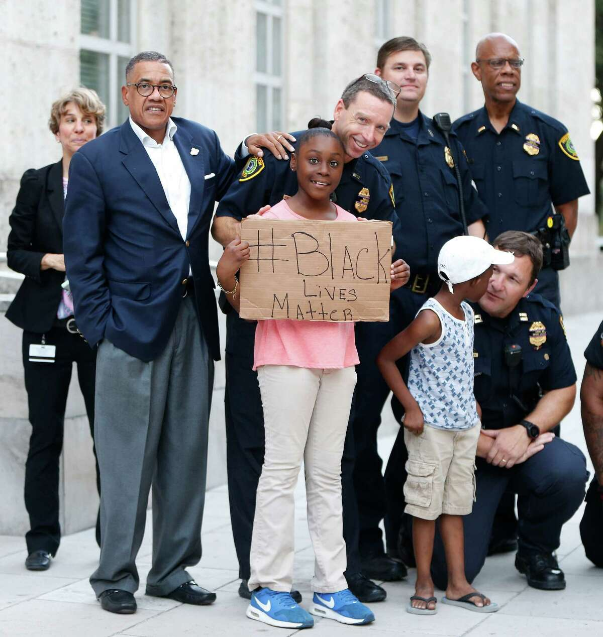 Houston police take photos with protesters during the rally that began at Discovery Green and ended at City Hall on Friday.
