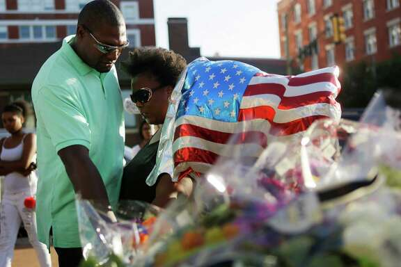 A couple reaches out and touches a police car where a memorial to the fallen police officers is growing outside of the Dallas Police Department on Lamar, Friday evening, July 8, 2016, in Dallas.