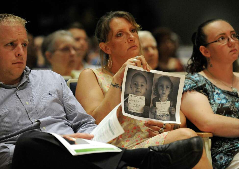 Loreen Hackett, center, holds photographs of her grandchildren corey Aldrich, 6-years-old, and his sister Alussia, 4, who have tested positive for PFOA contamination during a roundtable discussion held by U.S. Senator Kirsten Gillibrand at Hoosick Falls Central School on Friday July 8, 2016 in Hoosick falls, N.Y. (Michael P. Farrell/Times Union)