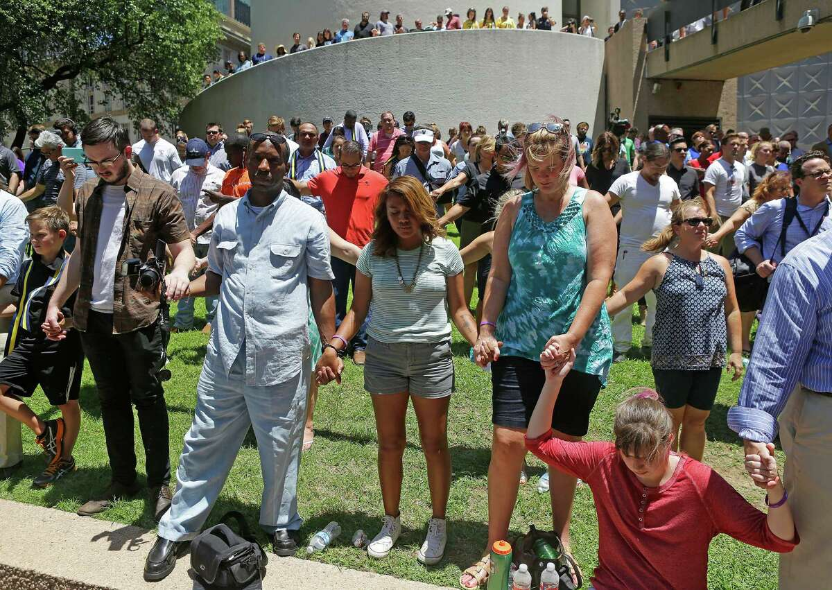 People hold hands while praying during an interfaith prayer vigil at Thanks-Giving Square, Friday, July 8, 2016, in Dallas.