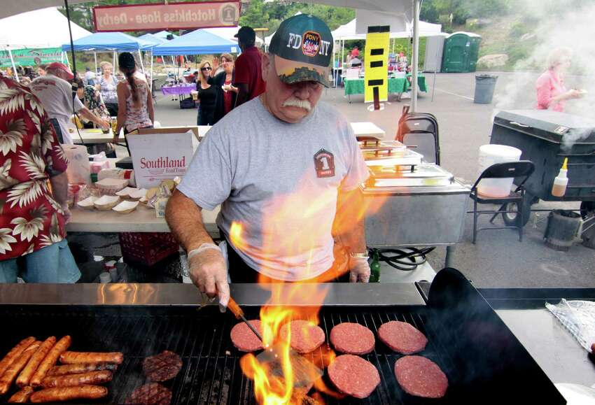 Voluteer Rich Tardie, with Hotchkiss Hose Company, grills up burgers and hot dogs during during St. Mary's Summer Festival held at St. Mary's Church grounds on Elizabeth Street in Derby, Conn., on Friday July 8, 2016. There is music played by DJ Megawatt along with food, crafts, a giant raffle and fun & games for the kids. Handicapped parking is behind the rectory.