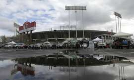 """FILE - In this Dec. 24, 2015, O.co Coliseum is reflected in a puddle before an NFL football game between the Oakland Raiders and the San Diego Chargers in Oakland, Calif. NFL Commissioner Roger Goodell says the existing stadiums in St. Louis, San Diego and Oakland are """"inadequate and unsatisfactory,"""" and that the proposals the Rams, Chargers and Raiders received to remain in their current cities lacked certainty. A person who has seen the report told The Associated Press on Saturday night, Jan. 9, 2016, that the NFL commissioner sent a 48-page report to team owners and cited a lack of longer-term solutions in plans to build new facilities. The person spoke on condition of anonymity because the league has not released details of the report. (AP Photo/Jeff Chiu, File)"""