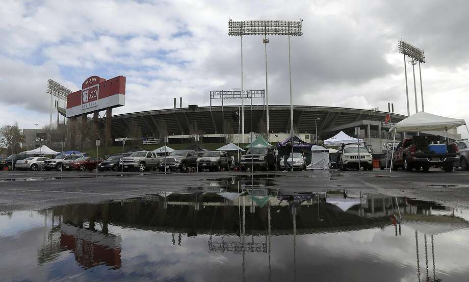 FILE - In this Dec. 24, 2015, Oakland Coliseum is reflected in a puddle before an NFL football game between the Oakland Raiders and the San Diego Chargers in Oakland, Calif. The city of Oakland said Wednesday night that it would be dropping its lawsuit against Alameda County over its sale of the Coliseum. Photo: Jeff Chiu, Associated Press
