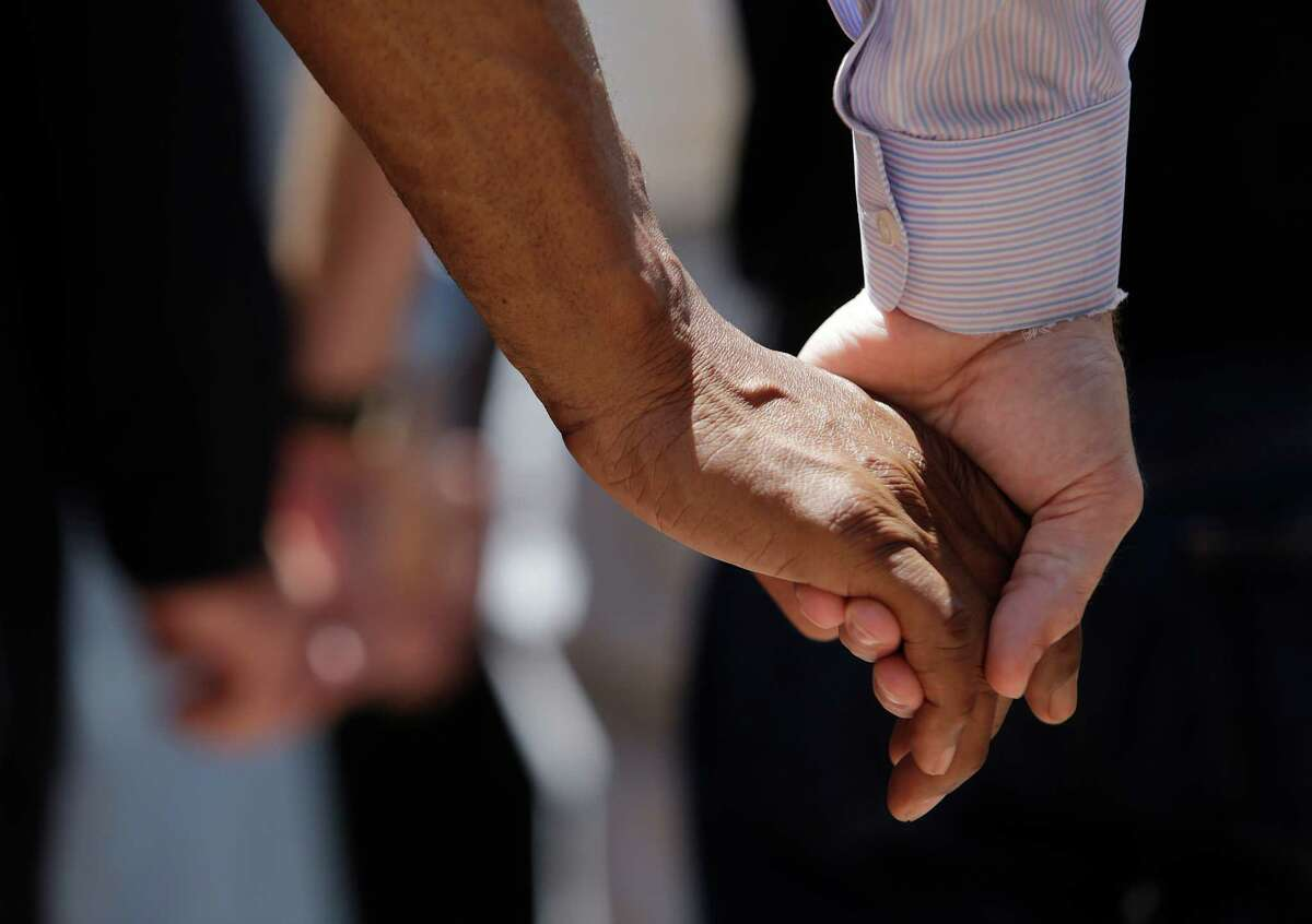 People clasp hands while praying during an interfaith vigil at Dallas' Thanks-Giving Square on Friday, a day after a sniper opened fire on police officers during a protest. Five were killed.