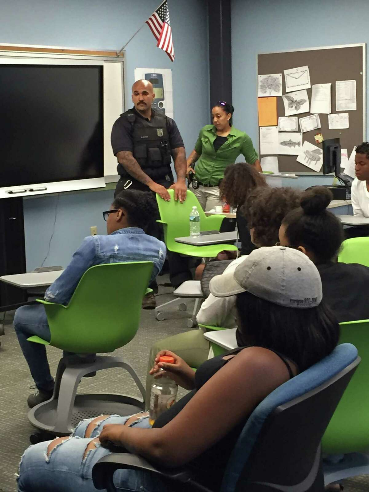 Albany Police officers George Brice, left, and Nicole Reddix, discuss with Albany teens how to remain safe while complying with orders during a police stop at a legal rights workshop organized by the Center for Law and Justice and held Friday at the Capital South Campus Center in Albany. (Paul Grondahl / Times Union)