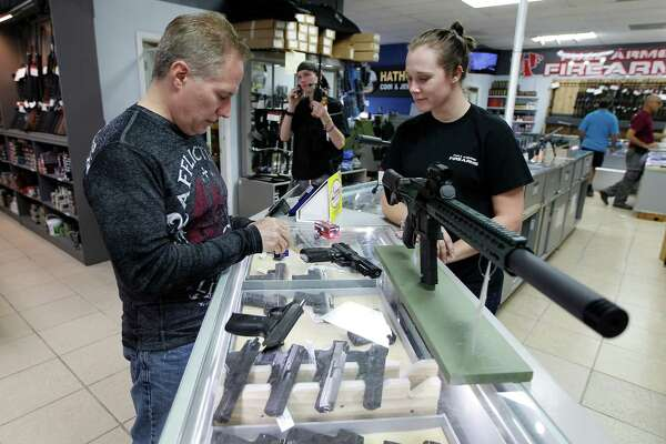 Johnnie Jackow (left) prepares to buy a new FN Herstal Five Seven 5.7 x 28 gun he purchased with the assistance of sales person Hanna Demorest at Full Armor Gun Range, 11911 Katy Freeway Monday, Dec. 7, 2015, in Houston.  ( Steve Gonzales  / Houston Chronicle )