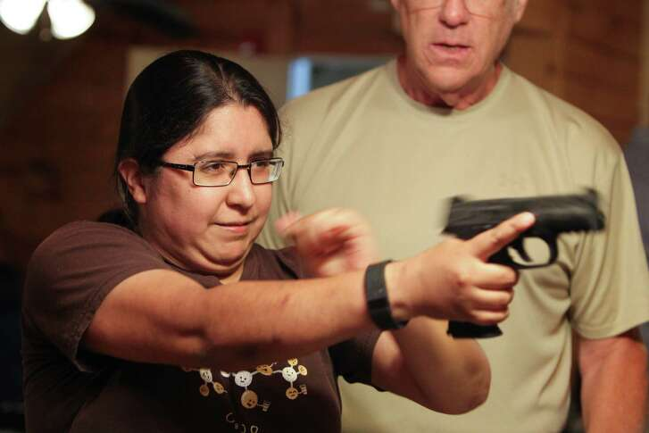 Rocio Dominguez learns the correct way to operate a weapon during a Shiloh Gun & 3D Archery license-to-carry class last month in Houston. Shares of gun makers received a boost after Thursday's attack on police officers in Dallas.