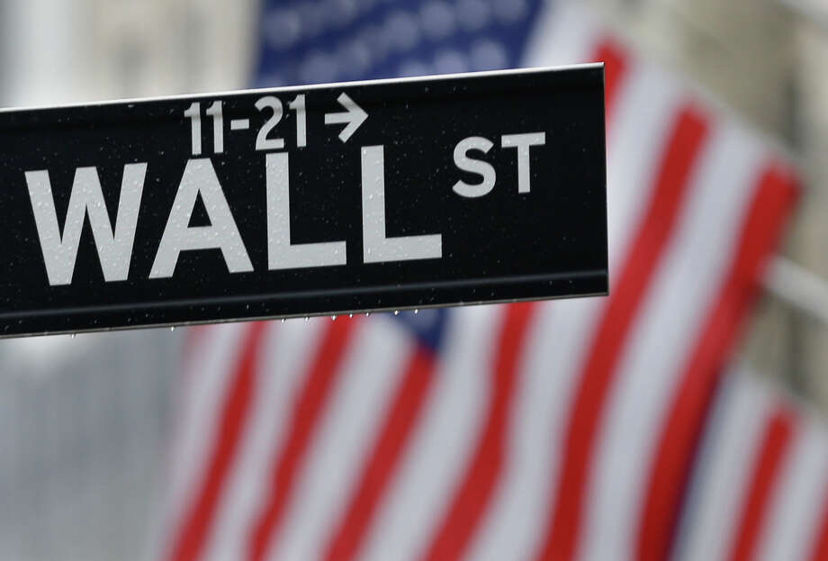 This July 9, 2015 photo shows a Wall Street sign near the New York Stock Exchange in New York.  Stocks are opening solidly higher on Wall Street after the government reported an encouraging burst of hiring last month. The gain of 287,000 jobs in June, which the Labor Department reported early Friday, July 8, 2016 was far more than economists were expecting. (AP Photo/Seth Wenig) Photo: Seth Wenig, STF / AP