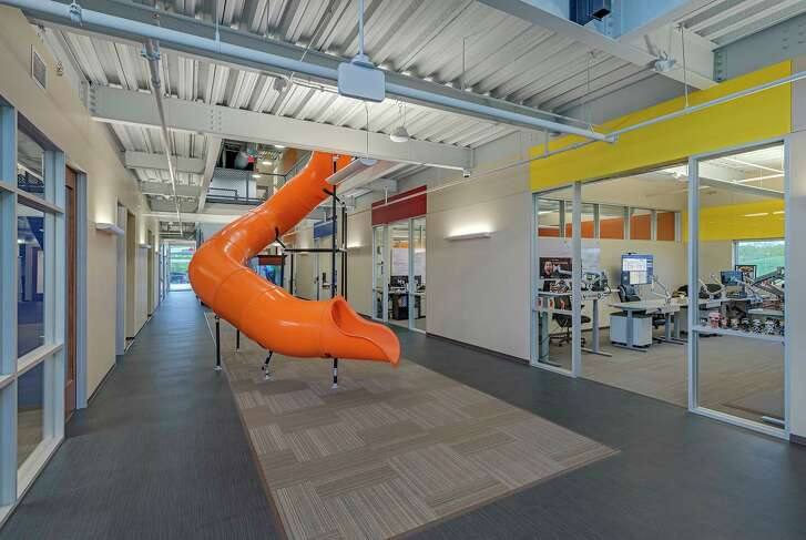 An adult slide in the lobby promotes fitness at Heavy Construction Systems Specialists' new office building for its software developers in Sugar Land.  Studio Red Architects designed the space.