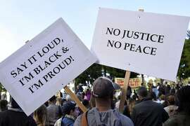 Javarre Wilson of Oakland holds a pair of signs as people gather at Justin Herman Plaza in San Francisco, Calif., on Friday, July 8, 2016,  to protest against recent police shootings in Minnesota and Louisiana.
