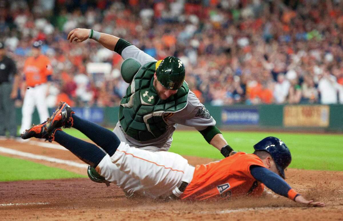 Oakland Athletics catcher Stephen Vogt, top, tags out the Houston Astros' Jose Altuve in the fifth inning of a baseball game Friday, July 8, 2016, in Houston. (AP Photo/George Bridges)