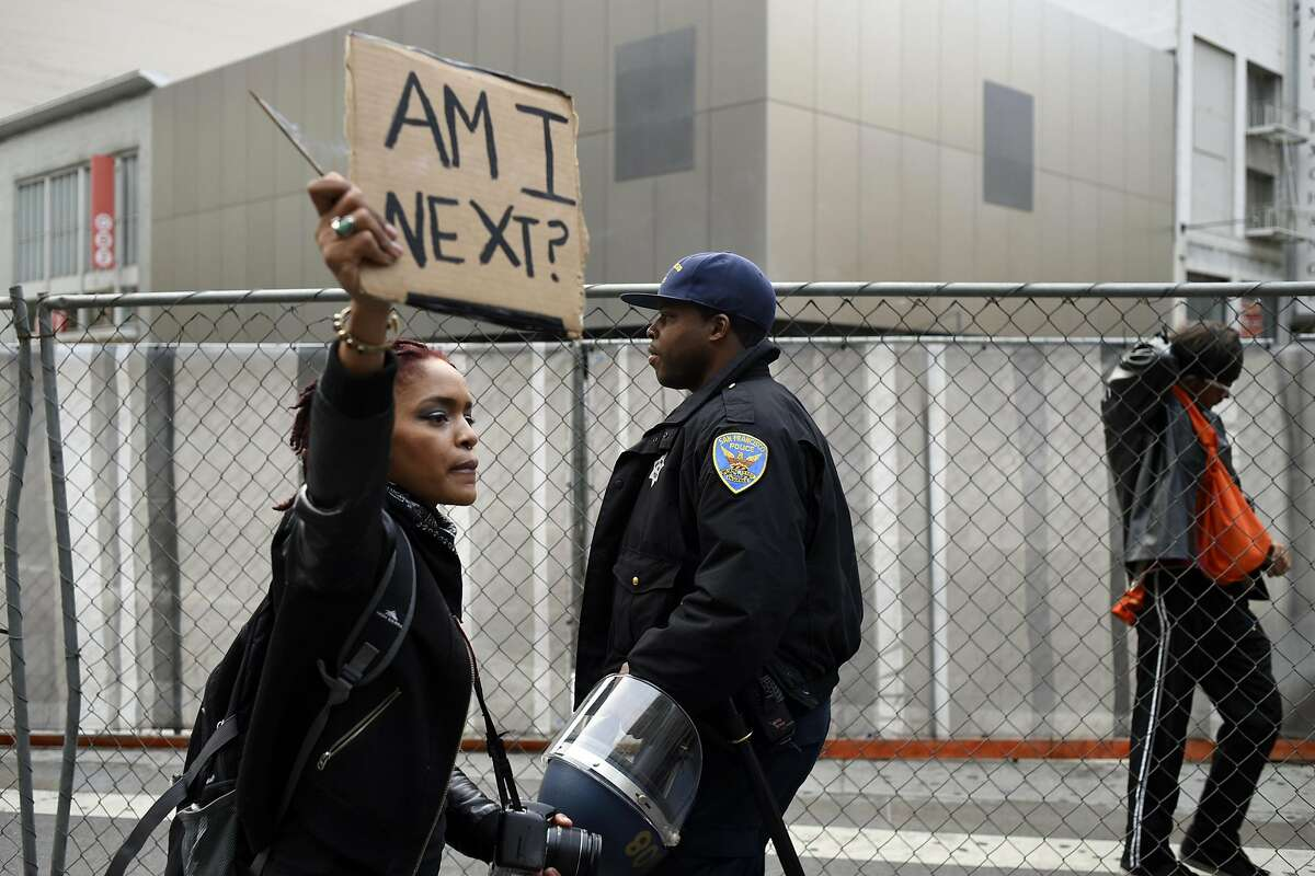 A woman who declined to give her name holds a sign near a police officer as protestors march down Market St. in San Francisco, Calif., on Friday, July 8, 2016, to protest against recent police shootings in Minnesota and Louisiana.