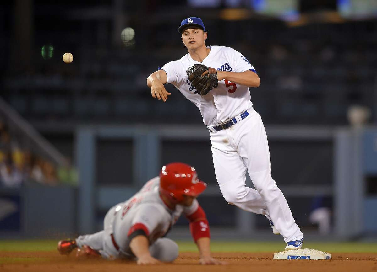 Cincinnati Reds' Joey Votto, below, is forced out at second as Los Angeles Dodgers shortstop Corey Seager throws out Brandon Phillips at first during the fourth inning of a baseball game, Monday, May 23, 2016, in Los Angeles. (AP Photo/Mark J. Terrill)