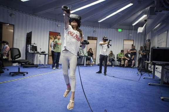 Bella Koelkebeck, 10, of San Francisco jumps while playing VR game at the Urban Safari Arcade on Friday, July 8, 2016 in San Francisco, California.
